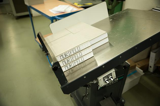 Die fertig zugeschnittenen Murifeldbücher auf der Auflage der Schneidmaschine