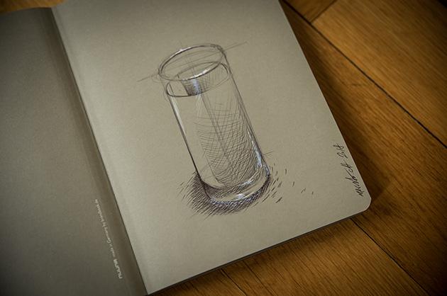nuuna not white – Gegenstandszeichnung eines Wasserglases mit Kugelschreiber und Weiss-Stift auf grauem Papier
