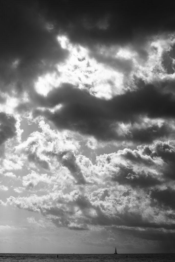 Elba. Sicht von den Felsen von Fetovaia aus aufs Meer. Wolken mit Segelschiff, Schwarz-Weiss