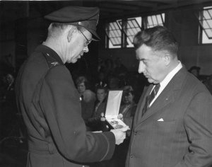 William J. Quish, Sr. accepts his son's Air Medal in a ceremony at Bradley Field, April 14, 1945. Quish was being liberated from his POW camp at about that time.