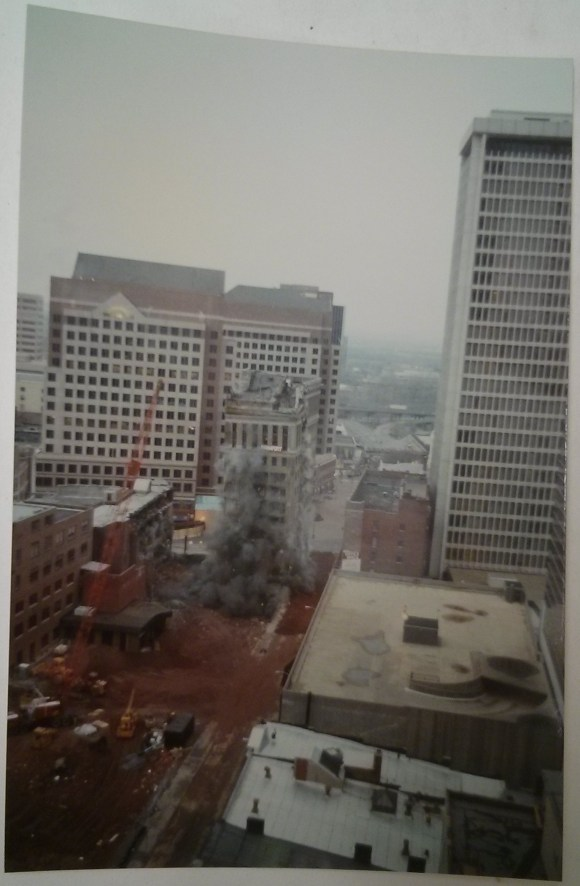 Hartford-Aetna Bank Building being imploded. The roof is caving in and there are clouds of smoke and dust coming from inside the building. Richard Welling. 2012.284.3544.