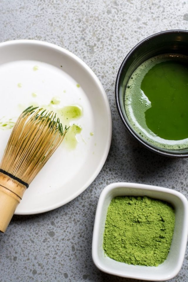 Matcha in bowl next to tea cup with green tea