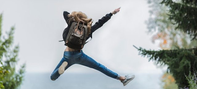Young lady wearing a backpack jumping