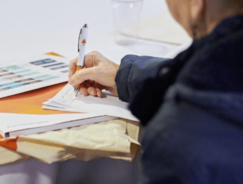 participant holding an MS Society pen filling out an MS Society survey