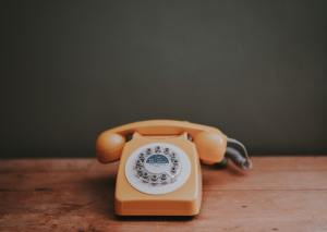An orange old-style telphone sitting on a wooden table