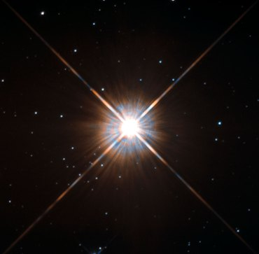 """Hubble Space Telescope image is our closest stellar neighbour: Proxima Centauri, just over four light-years from Earth. Although it looks bright through the eye of Hubble, Proxima Centauri -- with only about one eight the mass of our sun -- is not visible to the naked eye.Shining brightly in this Hubble image is our closest stellar neighbour: Proxima Centauri. Proxima Centauri lies in the constellation of Centaurus (The Centaur), just over four light-years from Earth. Although it looks bright through the eye of Hubble, as you might expect from the nearest star to the Solar System, Proxima Centauri is not visible to the naked eye. Its average luminosity is very low, and it is quite small compared to other stars, at only about an eighth of the mass of the Sun. However, on occasion, its brightness increases. Proxima is what is known as a """"flare star"""", meaning that convection processes within the star's body make it prone to random and dramatic changes in brightness. The convection processes not only trigger brilliant bursts of starlight but, combined with other factors, mean that Proxima Centauri is in for a very long life. Astronomers predict that this star will remain middle-aged — or a """"main sequence"""" star in astronomical terms —for another four trillion years, some 300 times the age of the current Universe. These observations were taken using Hubble's Wide Field and Planetary Camera 2 (WFPC2). Proxima Centauri is actually part of a triple star system — its two companions, Alpha Centauri A and B, lie out of frame. Although by cosmic standards it is a close neighbour, Proxima Centauri remains a point-like object even using Hubble's eagle-eyed vision, hinting at the vast scale of the Universe around us."""
