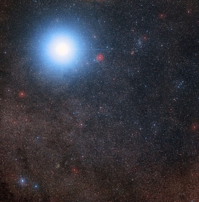 his image of the sky around the bright star Alpha Centauri A B also shows the much fainter red dwarf star, Proxima Centauri, the closest star to the Solar System. The picture was created from pictures forming part of the Digitized Sky Survey 2. The blue halo aroun d Alpha Centauri AB is an artifact of the photographic process, the star is really pale yellow in co lour like the Sun. Credit: Digitized Sky Survey 2 Acknowledgement: Davide De Martin/Mahdi Zamani