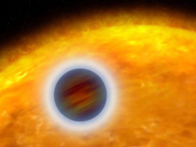 """An artist rendering of a """"hot Jupiter"""" extrasolar planet orbiting very close to its host star. The planet designated HD 209458b, is about the size of Jupiter. Unlike Jupiter, the planet is so hot that its atmosphere is """"puffed up."""" Starlight is heating the planet's atmosphere, causing hot gas to escape into space, like steam rising from a boiler. (NASA, ESA, and G. Bacon (STScI)."""