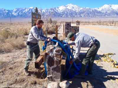 National Park Service staff begin the process of moving the California Registered Historical Landmark plaque, which was placed on the south side of the historic entrance road after it was removed from the front of the sentry post.
