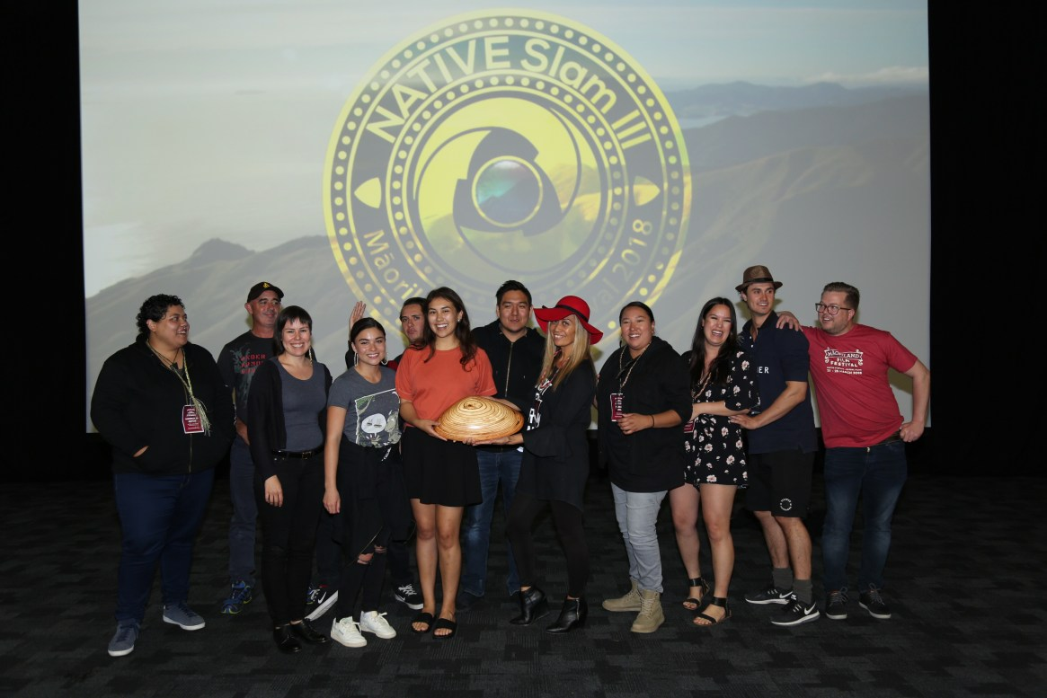 A group of filmmakers stand in front of a screen with the NATIVE Slam 3 logo behind them. In the centre a filmmaker holds a giant wooden pipi.