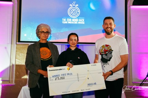 """Young girl holds a giant cheque for $5,000 and is flanked on either side by adults. The cheque says """"winner first prize"""" and in the background you can see """"2019 Indigihack Young Innovators Awards"""""""