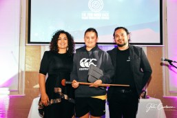 15 year old Te Ākauroa Jacob holds a jimal - firestick with Deline and Luke Briscoe in front of Indigihack logo