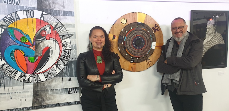 Artists Erena Koopu and Tā Derek Lardelli stand in front of pieces of Erena's artwork - a big painting and a sculpture