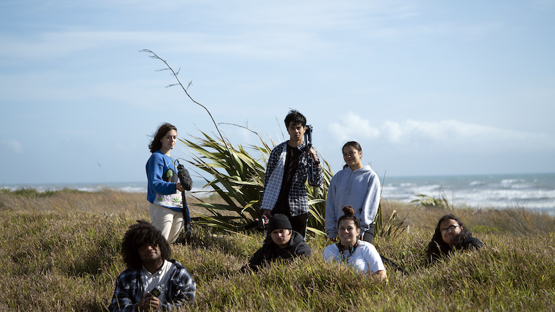 Image shows a group of teenagers standing broodily holding camera equipment on a wind swept grass dune with the beach in the background.