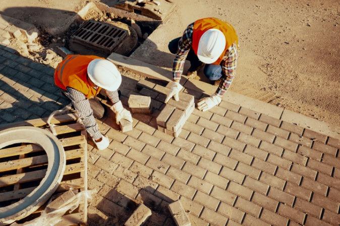 Construction workers at Mapa Group lay bricks