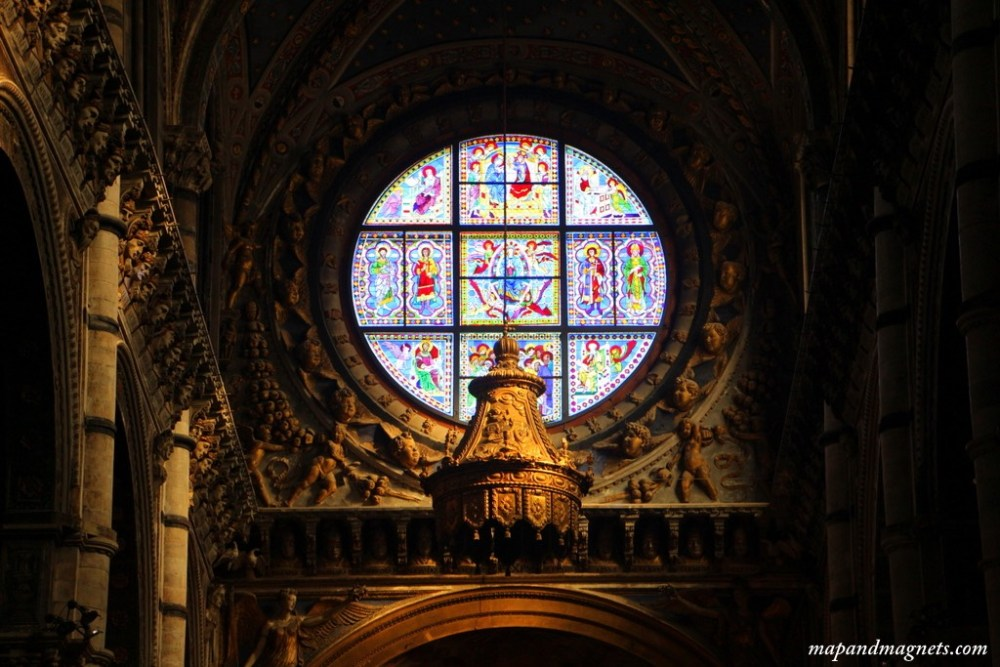 Stainglass and bell in cathedral Siena