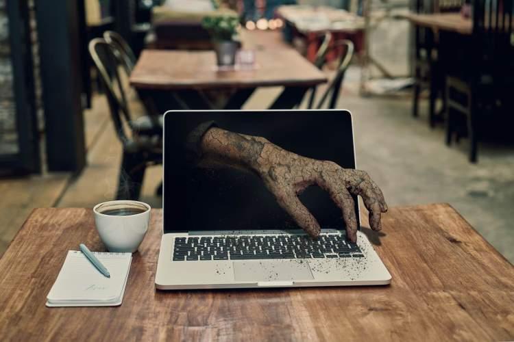 Main de zombie qui sort de l'écran d'un Mac.