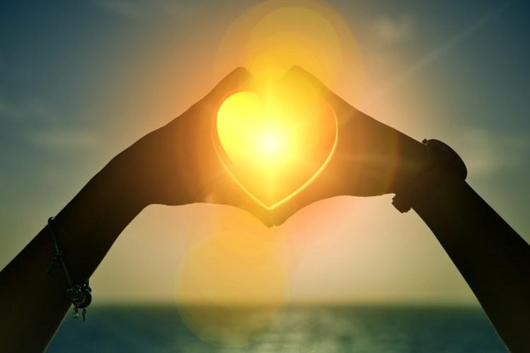 RETROUVER LA CONFIANCE AU CŒUR DE SOI - 2 mains forment un coeur autour du soleil