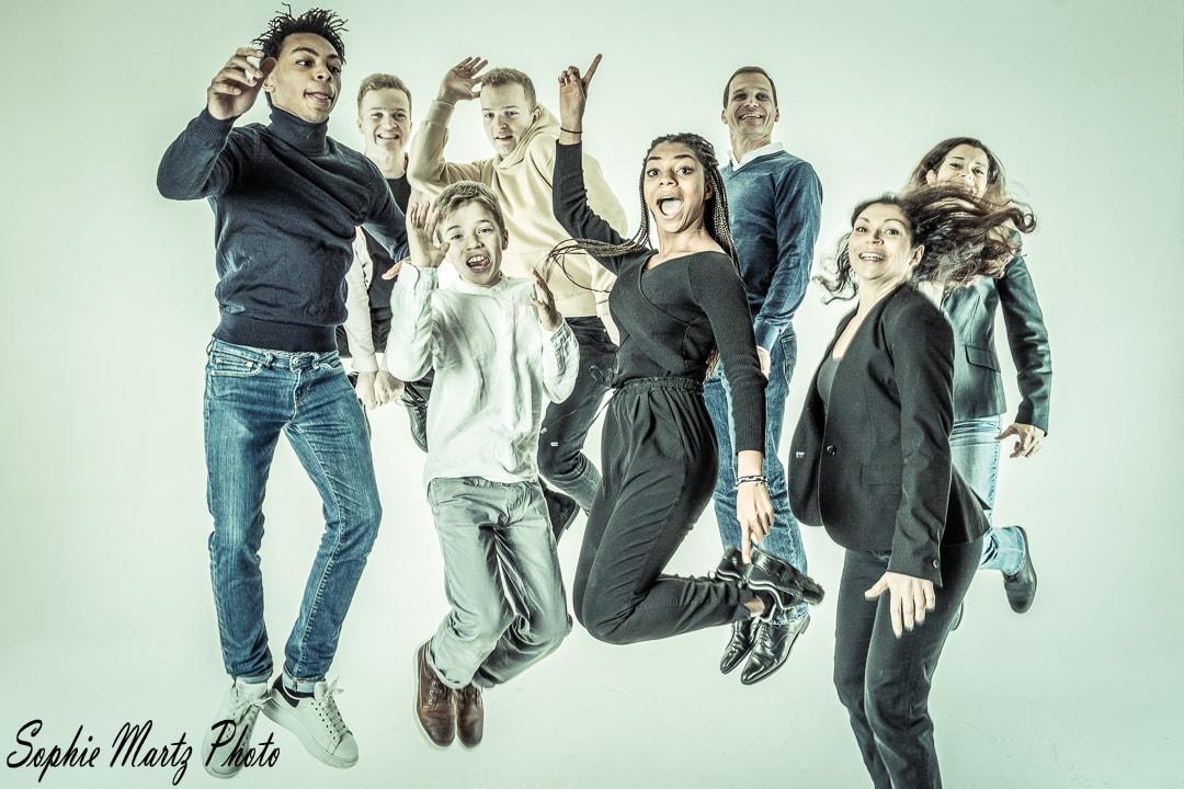 Famille métissée en train de sauter en studio photo