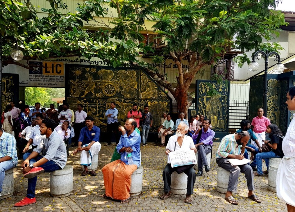 People sit on cement stumps at the entrance to SM Street in Kozhikode, waiting.