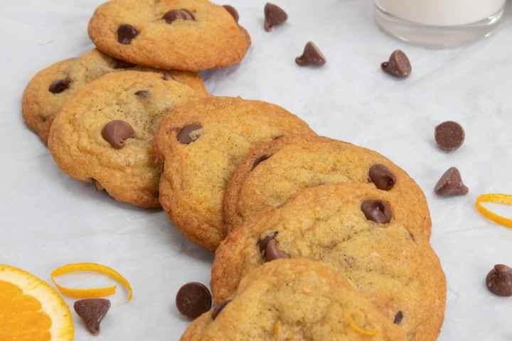 row of orange chocolate chip cookies with milk