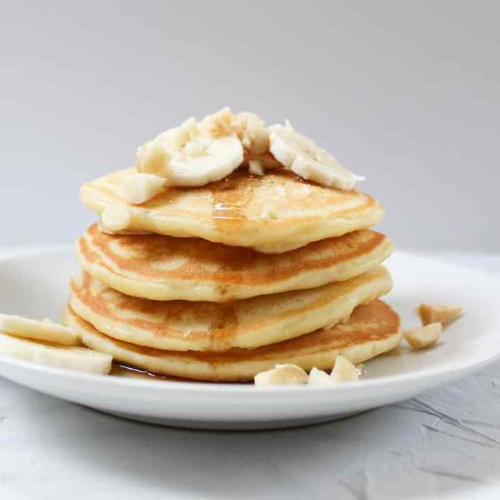 stack of banana macadamia nut pancakes with syrup