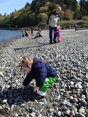 Picking a good rock to throw in the water, with Theresa latched on to Grampy in the background.