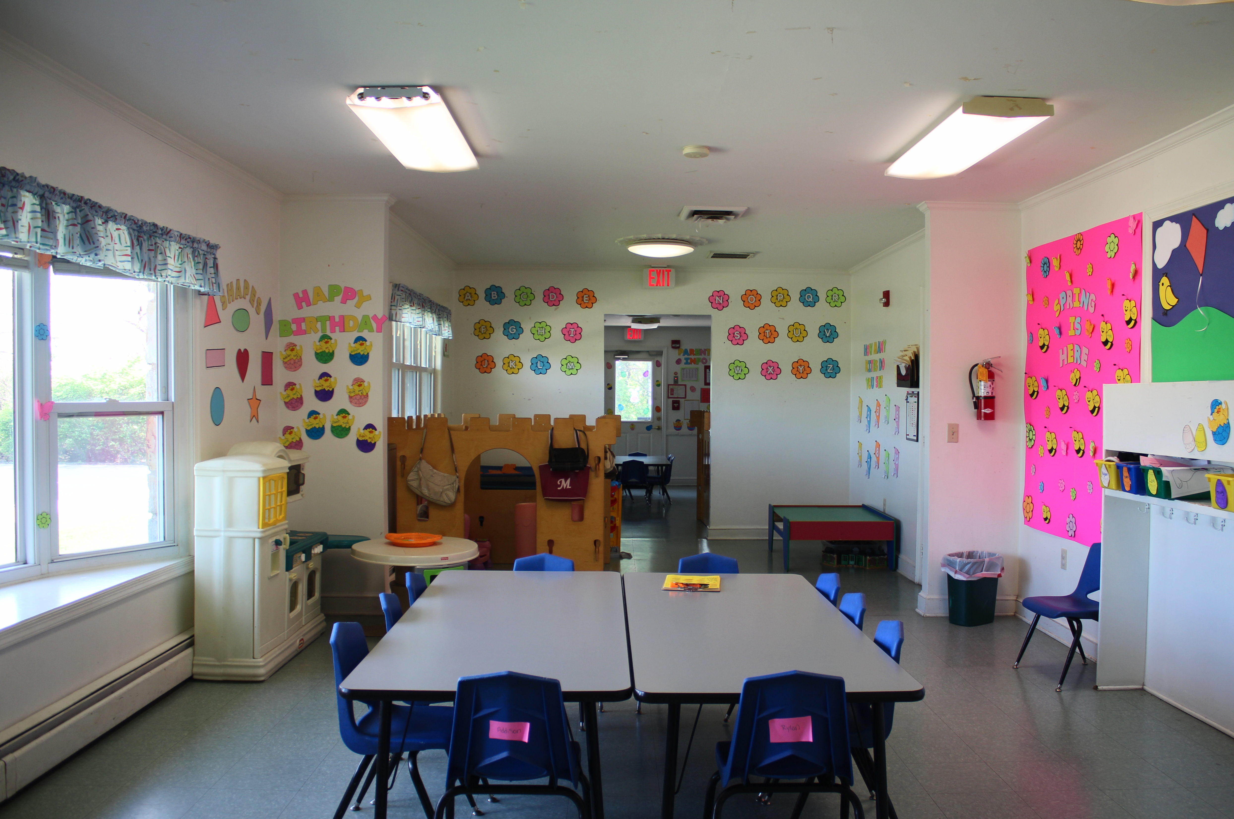 the classroom of Maplewood Childcare Center which has tables, desks, and lots of pictures on the wall.