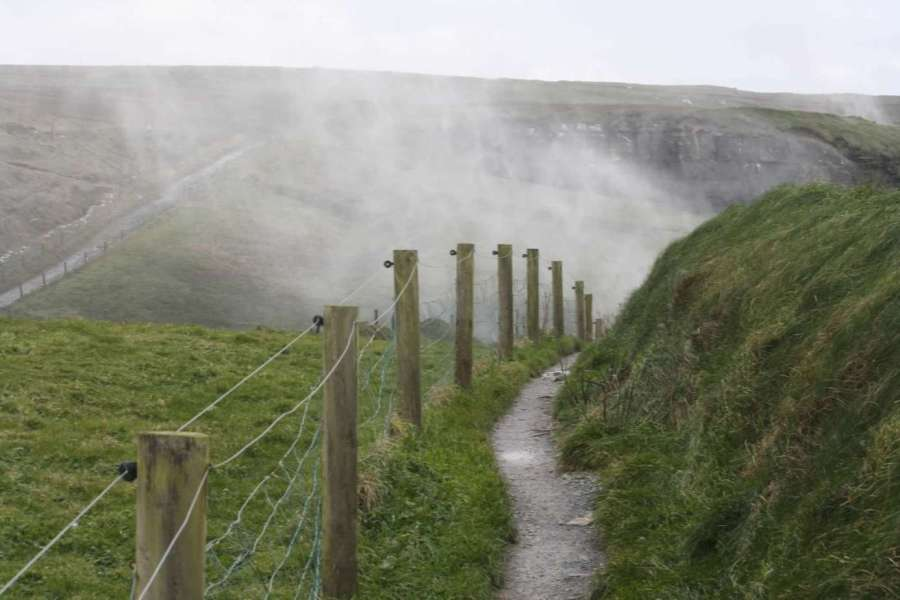 Ireland-hiking-the-cliffs-of-Moher-walking-trail-fence-mist-from-backwards-waterfalls