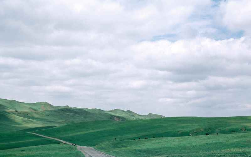 countryside road between green mountains under cloudy sky