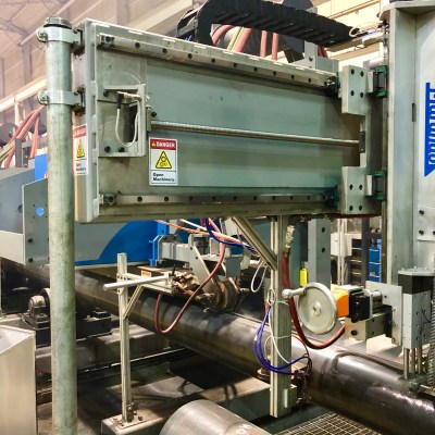 """A light green/grey inline weld inspection machine with """"Marando Industries"""" written down the side in blue is visible. It is inside of a manufacturing plant"""