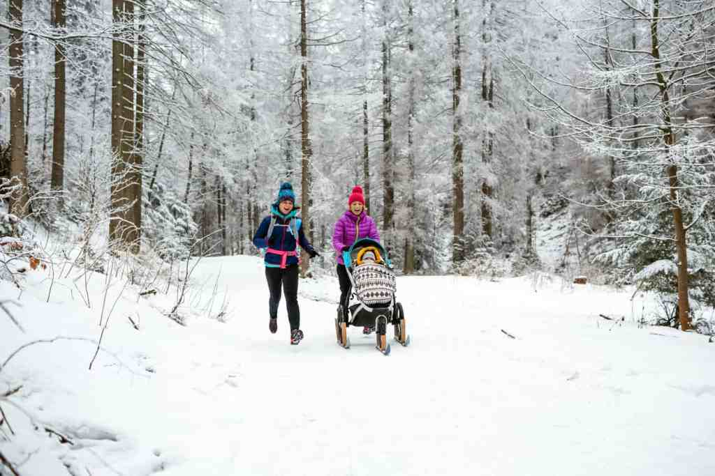 women running in the snowy woods - tips for running postpartum