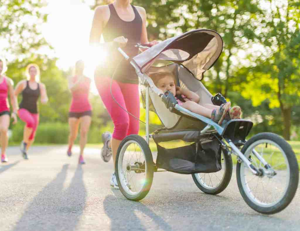 woman pushing child in stroller - tips for running postpartum