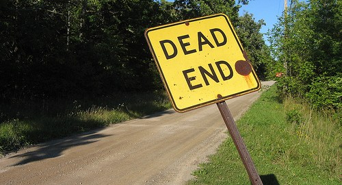 Photo of a dirt road with a crooked dead end sign