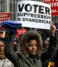 """Woman holding sign that says """"Voter Suppression is Unamerican"""""""