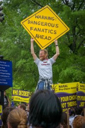 """Abortion Rights: Man holding sign, """"Warning: Dangerous Fanatics Ahead"""" during the March for Women's Lives, April 25, 2004"""