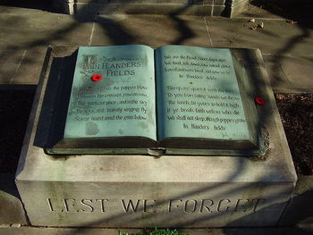 """Remembrance Day at the John McCrae House (birthplace, museum, & memorial) in Guelph, Ontario Canada. A detail shot of the """"altar"""" of the memorial, with the complete poem """"In Flander's Fields"""" & the line """"LEST WE FORGET"""" inscribed on it. 2 Canadian remembrance day poppy pins & part of a wreath are visible. Image source: Wikipedia"""
