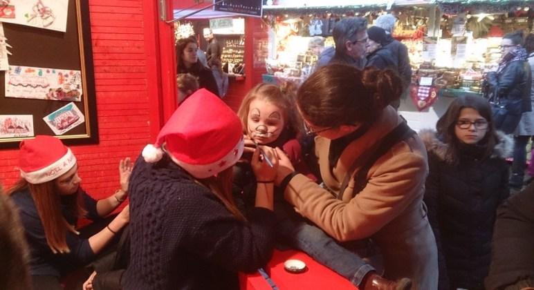 Une petite fille se fait maquiller pendant un atelier du marché de noël de Nantes