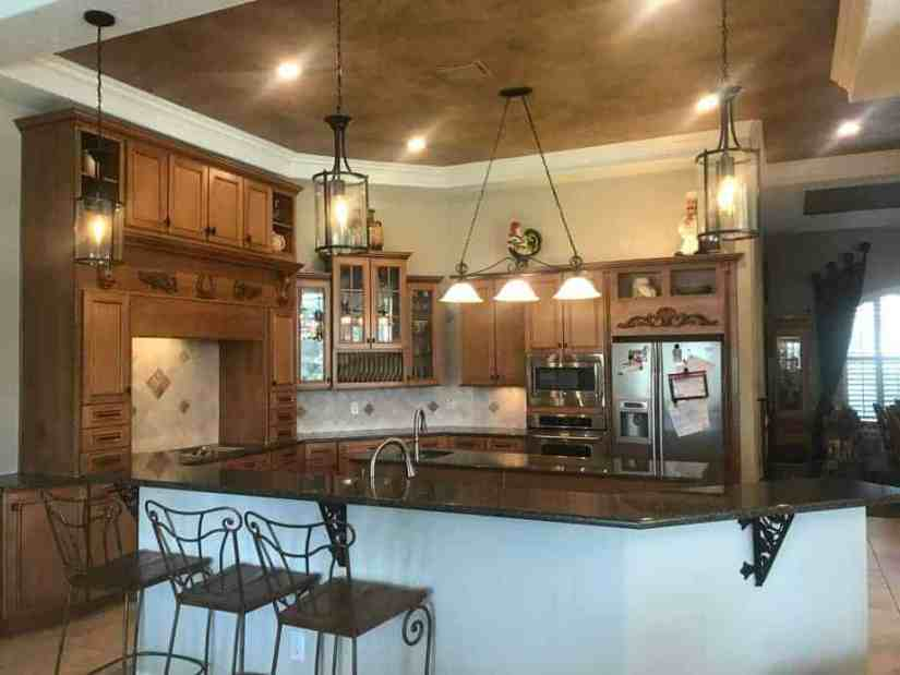 Wood cabinets, dark granite, painted ceiling accent