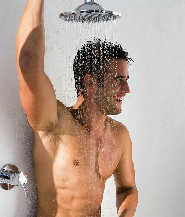 Homem tomando banho e esfoliando a pele