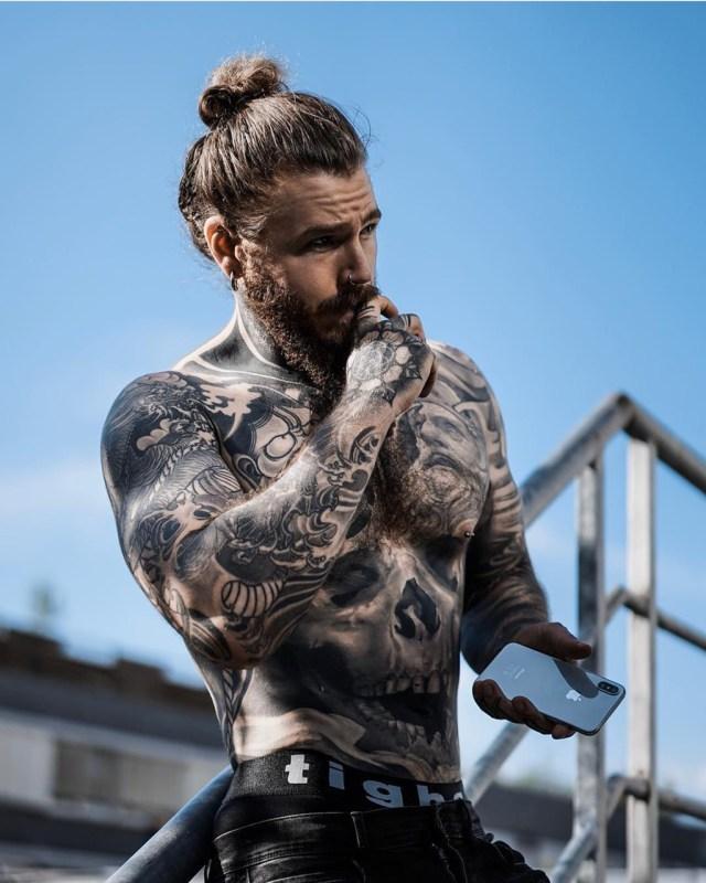 Homem tatuado com barba e coque
