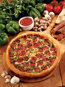 A pizza covered in pepperoni, green peppers and mushrooms sits on a table surrounded by marinara sauce, fresh peppers, tomatoes, mushrooms, garlic and pepperoni.