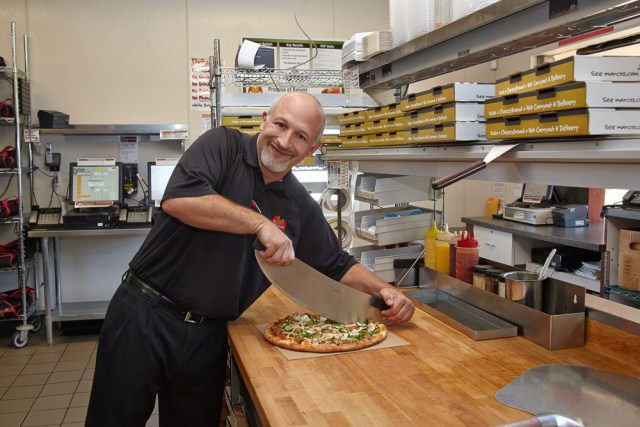 A Marco's Pizza franchise owner slices a pizza in the prep area of his restaurant.