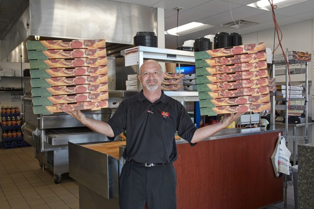 A Marco's franchisee balances more than a dozen pizza boxes between two hands in the prep area of his restaurant.