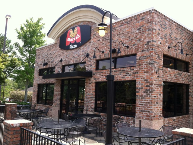 The exterior of a Marco's Pizza location with tables in the patio area.