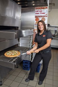 Franchisee Ashley Jones poses as she pulls a fresh pizza out of the oven in one of her restaurants.