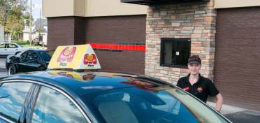 A smiling Marco's Pizza franchise employee stands by the driver-side door of a car with a Marco's Pizza delivery topper in front of the drive-thru window of the restaurant.