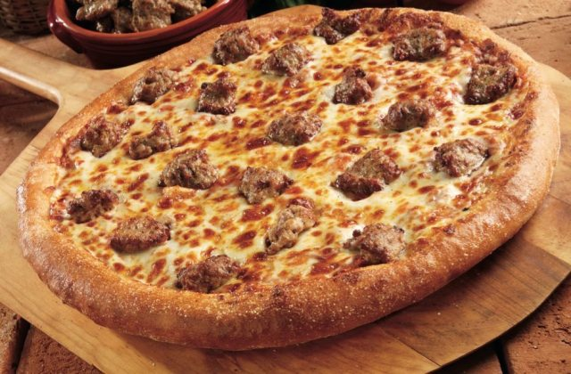 A fresh, hot sausage pizza cooling on a wooden serving board.