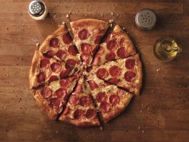 An overhead shot of a sliced pepperoni pizza on a wooden table surrounded by a carafe of olive oil and jars of red pepper flakes and parmesan cheese.