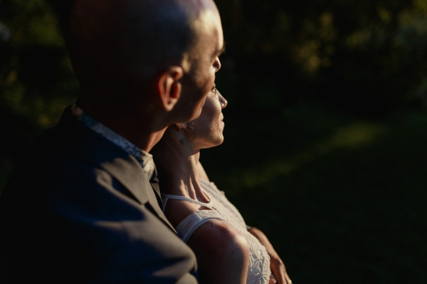 groom holding the bride at sunset